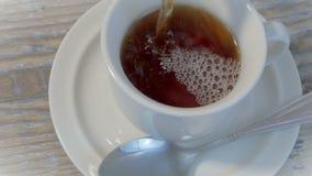 Versez le thé dans une tasse 4K banque de vidéos
