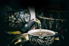 Versez le thé de la théière dans le rétro concept Photos stock
