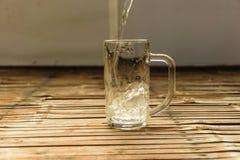 Versez un verre de l'eau sur une table en bois Images stock