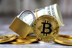 Versión física del nuevo dinero virtual de Bitcoin, del candado de oro y de billetes de banco de un dólar imagenes de archivo