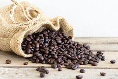 Versi i chicchi di caffè dal sacco sul pavimento di legno Fotografia Stock Libera da Diritti