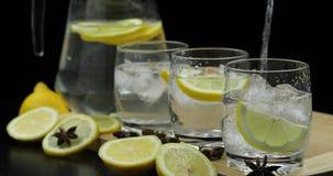 Versi il succo di limone in vetro con le fette del limone e del ghiaccio Cocktail alcolico del limone fotografia stock libera da diritti