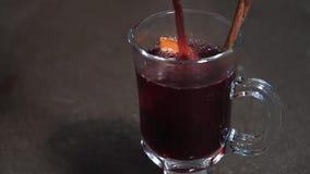 Versi il vino rosso caldo con i frutti e le spezie in un vetro Vino sciupato Lento-Mo archivi video