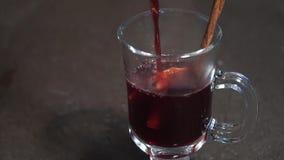 Versi il vino rosso caldo con i frutti e le spezie in un vetro Vino sciupato Lento-Mo stock footage