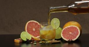 Versi il whiskey, il cognac, liquore da una bottiglia in una tazza di vetro immagine stock