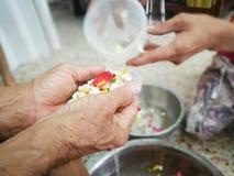 Versi l'acqua sulle mani degli anziani riveriti e chieda benedire Fotografie Stock Libere da Diritti