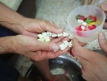 Versi l'acqua sulle mani degli anziani riveriti e chieda benedire Fotografia Stock