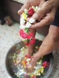 Versi l'acqua sulle mani degli anziani riveriti e chieda benedire Immagini Stock
