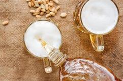 Versi la birra in un vetro da una bottiglia fotografie stock