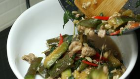 Versi le melanzane fritte scalpore con carne di maiale tritata, le foglie di erbe del basilico, peperone dolce rosso dalla pentol stock footage