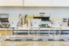 Versi sopra la macchinetta del caffè del caffè blu famoso della bottiglia immagine stock libera da diritti