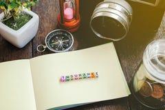 VERSICHERUNGS-Wortblock mit Lichteffekt Weinlesekamera, Kompass, Münzen im Glas und hölzerner Hintergrund Lizenzfreie Stockfotografie