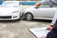 Versicherungsagent überprüfen Berichts-Antragsformular des beschädigten Fahrzeugs und der Archivierung stockfotos