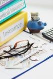 Versicherungsform, -ordner, -Sparschwein, -gläser und -geld Lizenzfreie Stockbilder