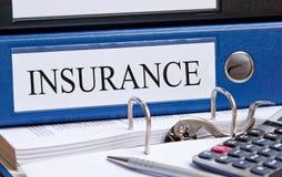 Versicherungsmappe auf Schreibtisch Stockfotos