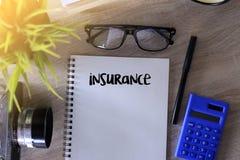 Versicherungswortschreiben auf Notizbuch auf Holztisch Stockbild