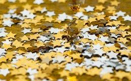 Versieht das glänzende Weihnachten mit einem Sternchen, das auf einen Goldhintergrund zerstreut wird Stockbild