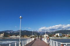 Versilia. The pedestrian ponton in Marina di Massa with in background the Apuan Alps, Tuscany, Italy Royalty Free Stock Images