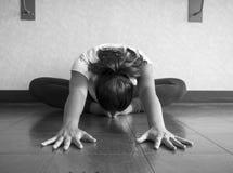 Versione in bianco e nero dell'allungamento di Hip del ballerino di yoga nella posizione della farfalla che raggiunge testa di an Immagine Stock