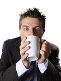 Verslaafden bedrijfsmens in kostuum en band het drinken kop van koffie bezorgd en gek in cafeïneverslaving Stock Foto