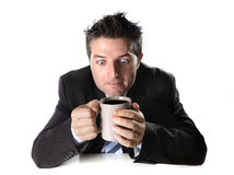Verslaafden bedrijfsmens in kostuum en bandholdingskop van koffie bezorgd en gek in cafeïneverslaving Stock Fotografie