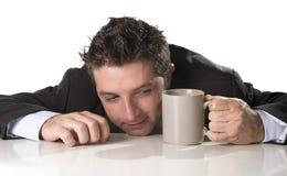 Verslaafdenzakenman in kostuum en bandholdingskop van koffie als maniak in cafeïneverslaving Stock Afbeeldingen