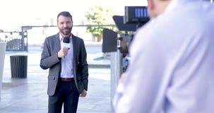 Verslaggever die het nieuws in openlucht behandelen stock videobeelden