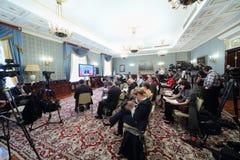 Verslaggevers en cameralieden het werk aangaande Vergrote vergadering Stock Fotografie