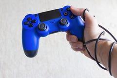 Verslaving aan videospelletjesconcept, blauw spelstootkussen met verpakte hand Stock Fotografie