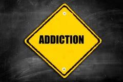 Verslaving die op voorzichtigheidsteken wordt geschreven stock afbeeldingen