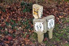Versleten concrete Britse Britse Sluitklep en Hydranttekens op blad behandelde grond Royalty-vrije Stock Foto