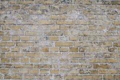 Versleten Doorstane Vuile Gele Bakstenen muurachtergrond Stock Afbeeldingen