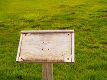 Versleten houten teken op grasrijk gebied Stock Afbeelding