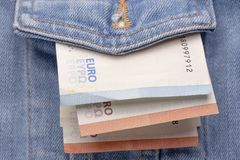 Versleten klassiek denimjasje vooraan met een kleine hoeveelheid euro bankbiljetten stock foto's