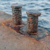 Versleten roestige meerpalen op oude concrete pijler stock foto