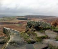 Versleten rotsen en een mening over de weg die aan Stanage-het gezicht van de Randrots leiden stock afbeelding