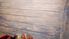 Versnelde lengte van een mens die over de houten raad met witte verf schilderen stock video