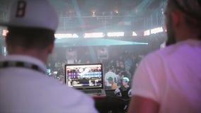 Verso DJ que gira na plataforma giratória no partido no clube noturno luzes Menino de Mc multidão filme