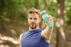 Verso uno stile di vita più sano Acqua della bevanda dell'atleta dopo la formazione nel parco L'aspetto atletico dell'uomo tiene  fotografia stock libera da diritti