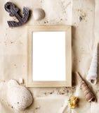 Verspotten hölzerner Fotorahmen der Weinlese auf Kraftpapier mit Sand- und Seeoberteilen oben lizenzfreie stockbilder