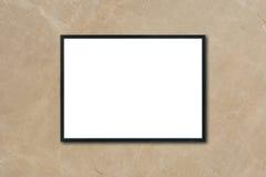 Verspotten Sie herauf den leeren PlakatBilderrahmen, der an der braunen Marmorwand im Raum hängt Stockfotografie