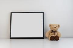 Verspotten Sie herauf Fotorahmen auf Tabelle mit einem Teddybären als Dekoration Lizenzfreie Stockfotos
