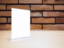 Verspotten Sie herauf Menü-Feldschablone auf Tabelle Stangen-Backsteinmauerhintergrund Stockfotografie