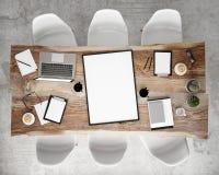 Verspotten Sie herauf Plakatrahmen auf SitzungsKonferenztische mit Bürozubehör und Laptop-Computer, Hippie-Innenhintergrund, Stockfoto