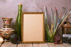 Verspotten Sie herauf Plakatrahmen mit künstlerischen Gegenständen der Weinlese und alte Kamera auf Holztisch Lizenzfreie Stockbilder