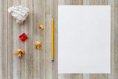 Verspotten Sie oben mit Weißbuchblatt, -bleistift, -schnitzeln und -bleistiftspitzer auf hölzernem Hintergrund Lizenzfreies Stockfoto
