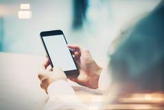 Verspotten Sie oben von der Hand der Mädchen unter Verwendung des intelligenten Telefons im Café Stockfotografie