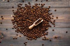 Verspreide koffiebonen en bonen in lepel op de donkere houten mening van de lijstbovenkant Klaar voor gebruik Stock Afbeelding