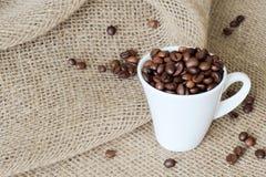Verspreide koffiebonen en witte exclusieve die porseleinkop met geurige geroosterde koffiebonen worden gevuld bij jute het ontsla stock foto's