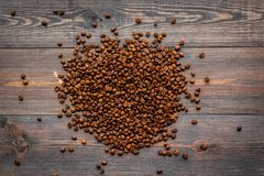 Verspreide koffiebonen op de donkere houten mening van de lijstbovenkant Klaar voor gebruik Royalty-vrije Stock Foto